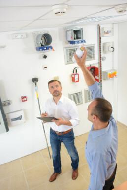 Brandskyddskontrollant inspekterar brandlarm