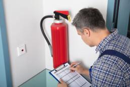 Man som gör en checklista över brandskydd på ett företag.